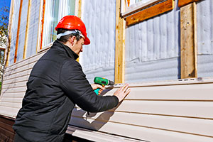 Technician Applying House Siding